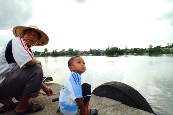 魚釣りをする親子