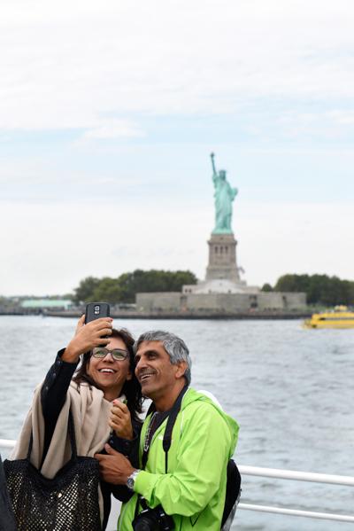 自由の女神を見て写真を撮る観光客の笑顔